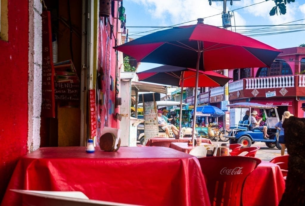 Outdoor restaurant in Mexico with red tablecloths and red umbrellas shading the tables