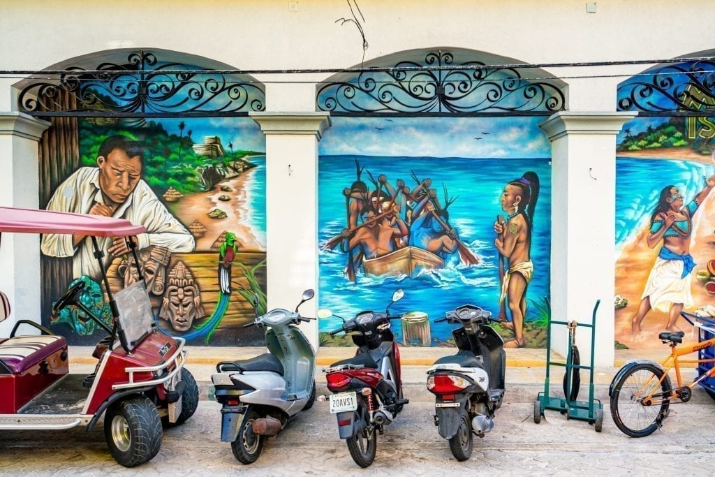 Street art in Isla Mujeres Mexico with mopeds and a golf cart parked in front of the building it is on. The street art depicts Mayan culture.