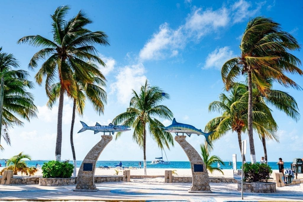 Palm trees and columns topped with shark figurines framing the entrance to a beach on Isla Mujeres