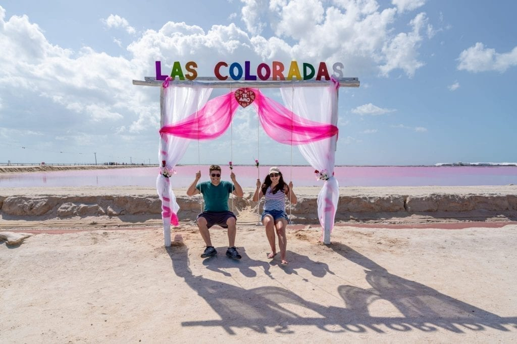 Kate Storm and Jeremy Storm sitting in swings in front of the pink lakes las coloradas mexico