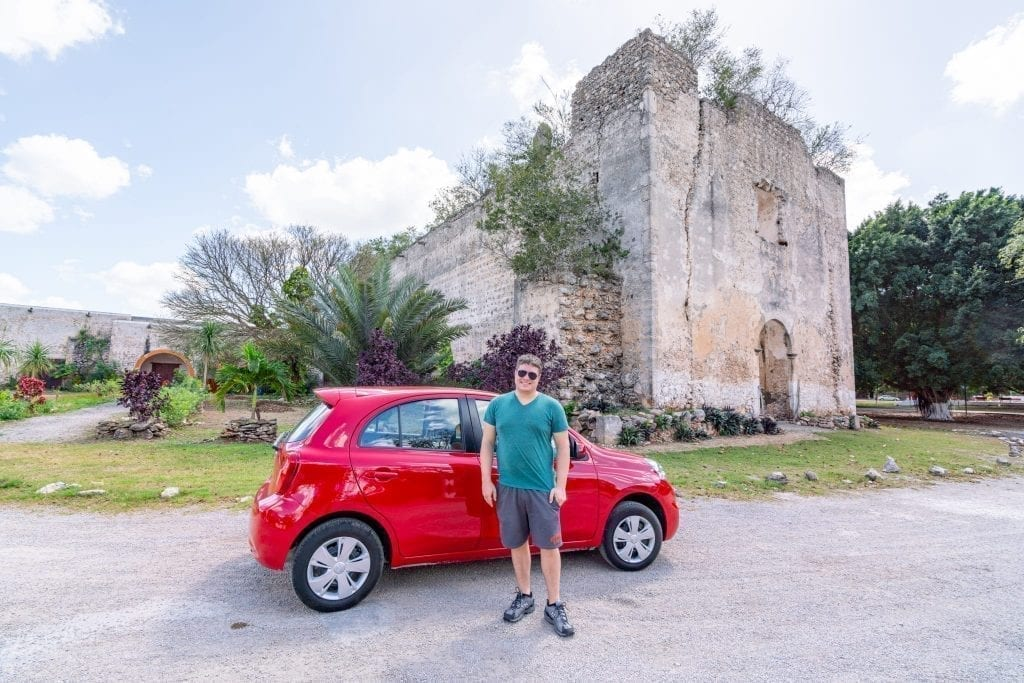 Jeremy Storm standing in front of a red car parked in front of a church as part of a road trip Yucatan itinerary