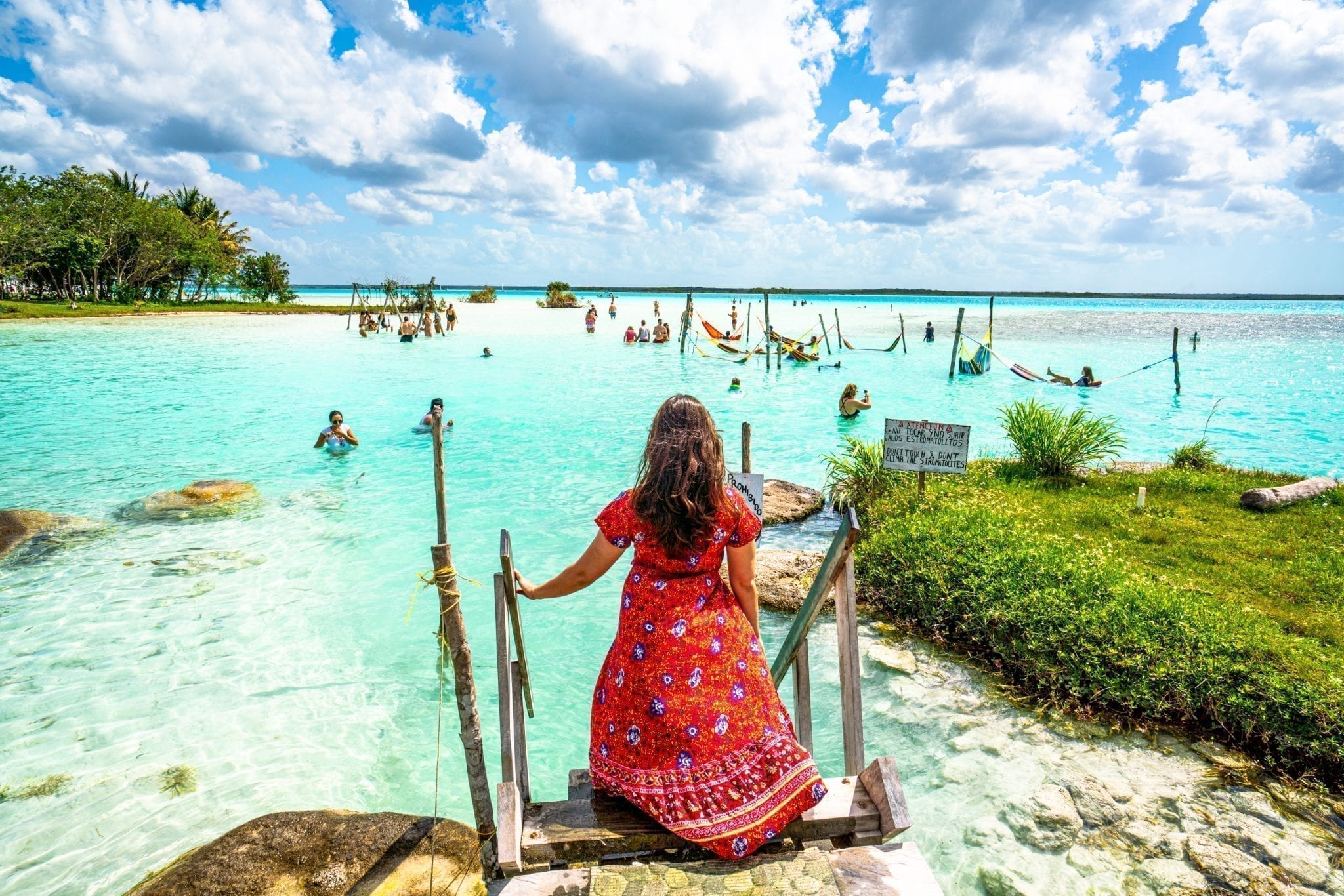 kate storm in a red dress in bacalar mexico, how to save money to travel the world helped us reach this destination