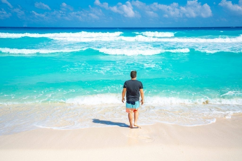 Jeremy Storm walking into a turquoise sea in Cancun Mexico