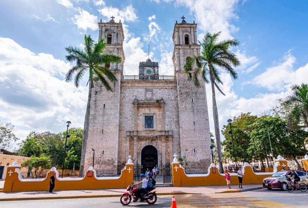 Valladolid Cathedral with a motorbike passing by in front of it. Valladolid is an excellent base during this first part of this Mexico road trip itinerary
