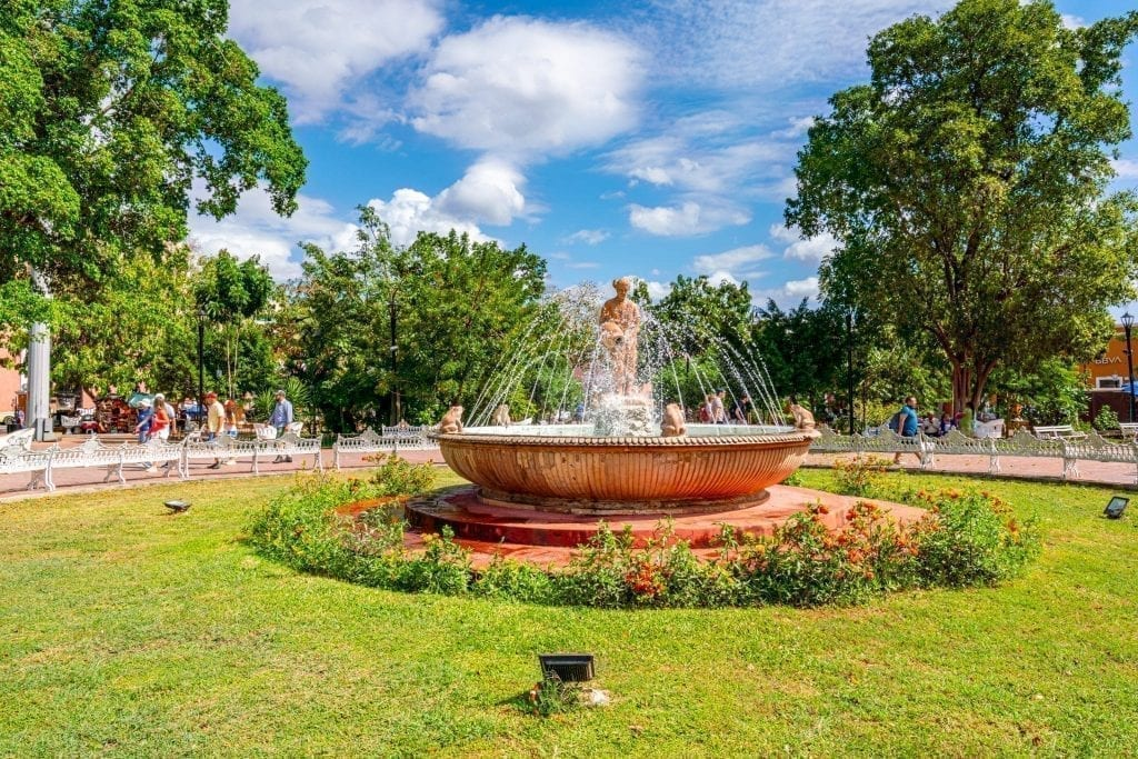 fountain in the center of the zocalo surrounded by a green lawn