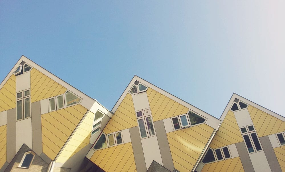Yellow cube houses of Rotterdam with blue sky above them. Rotterdam is an excellent European hidden gem to visit