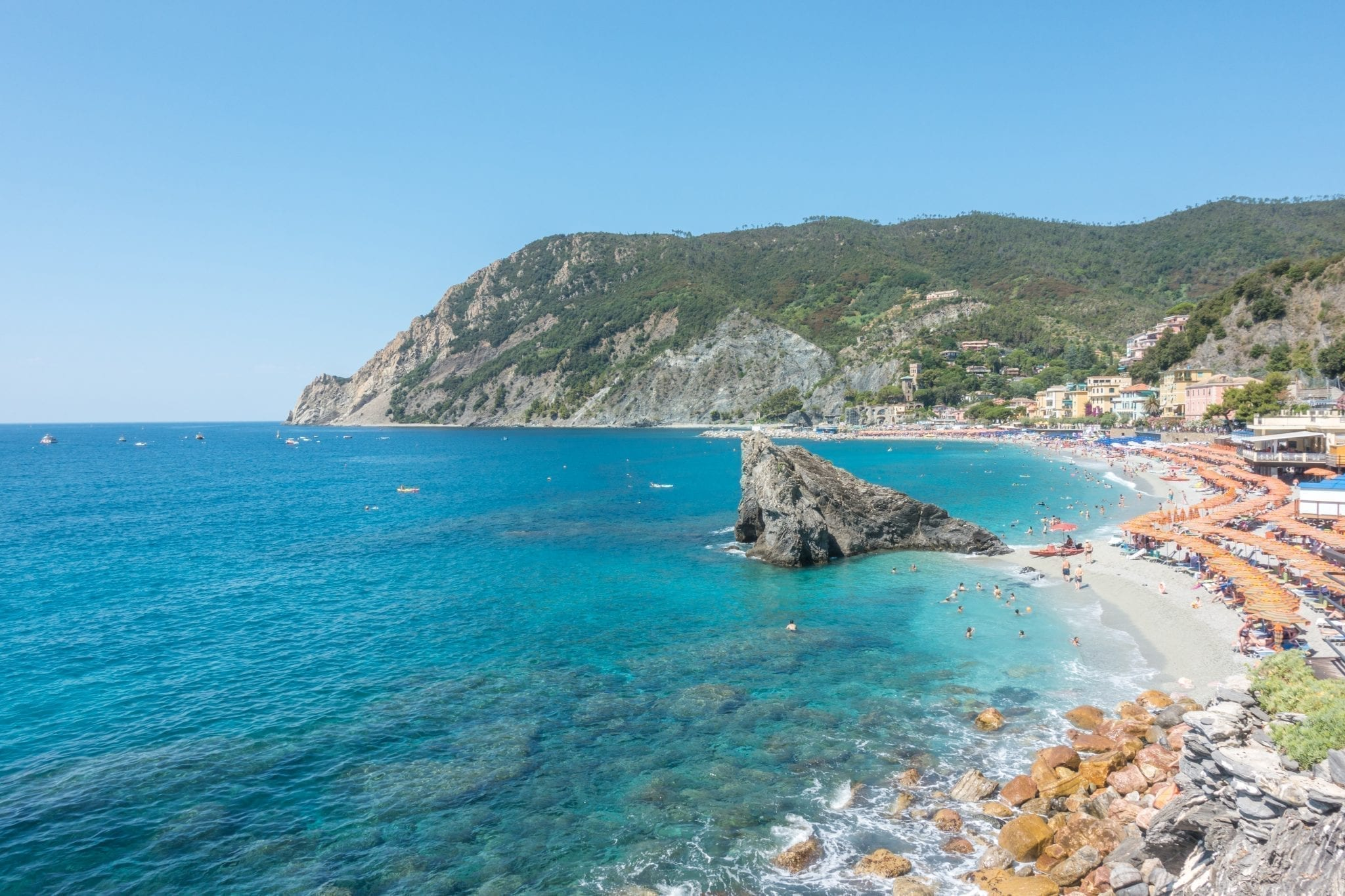 View of Monterosso al Mare beach from above on a sunny day, umbrellas are visible on the right side of the photo. This beach is one of the most instagrammable places in Cinque Terre!