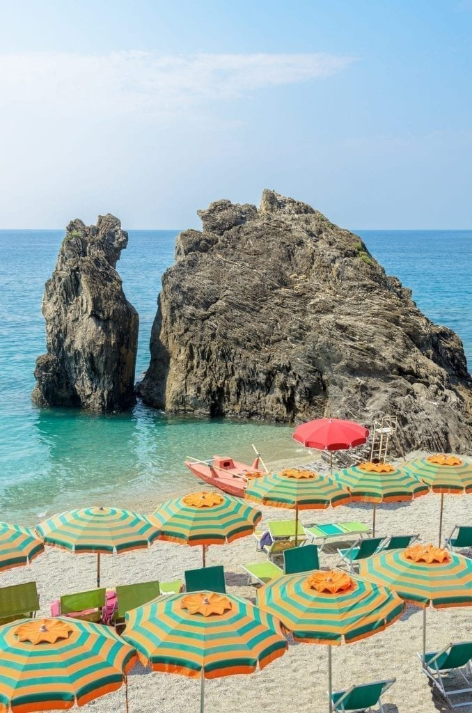View of Spiaggia di Fegina in Monterosso al Mare with colorful umbrellas in the foreground, one of the best photography locations in Cinque Terre Italy