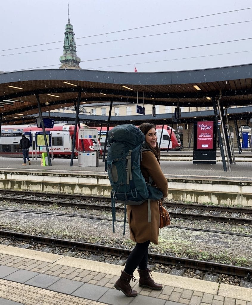 Kate Storm waiting for a train on a platform in Luxembourg, as part of a travel Europe by train adventure across Europe
