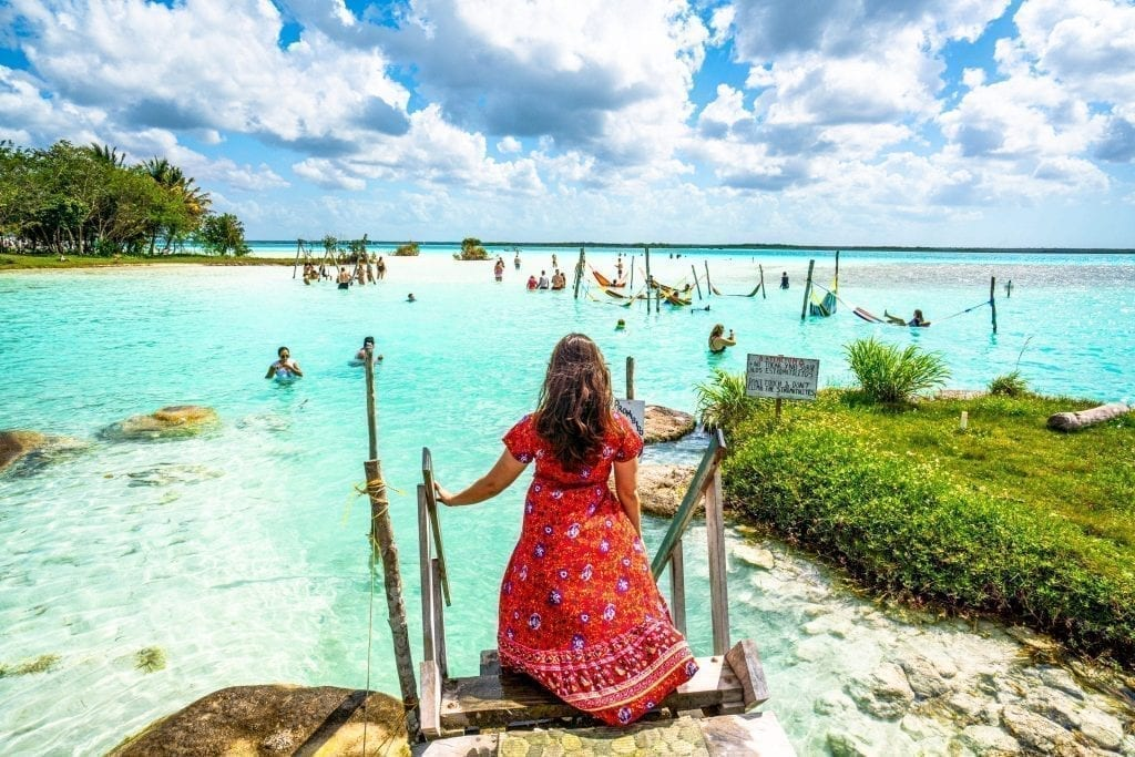 Kate Storm in a red dress at Cocalitos Bacalar during a road trip Yucatan travel itinerary