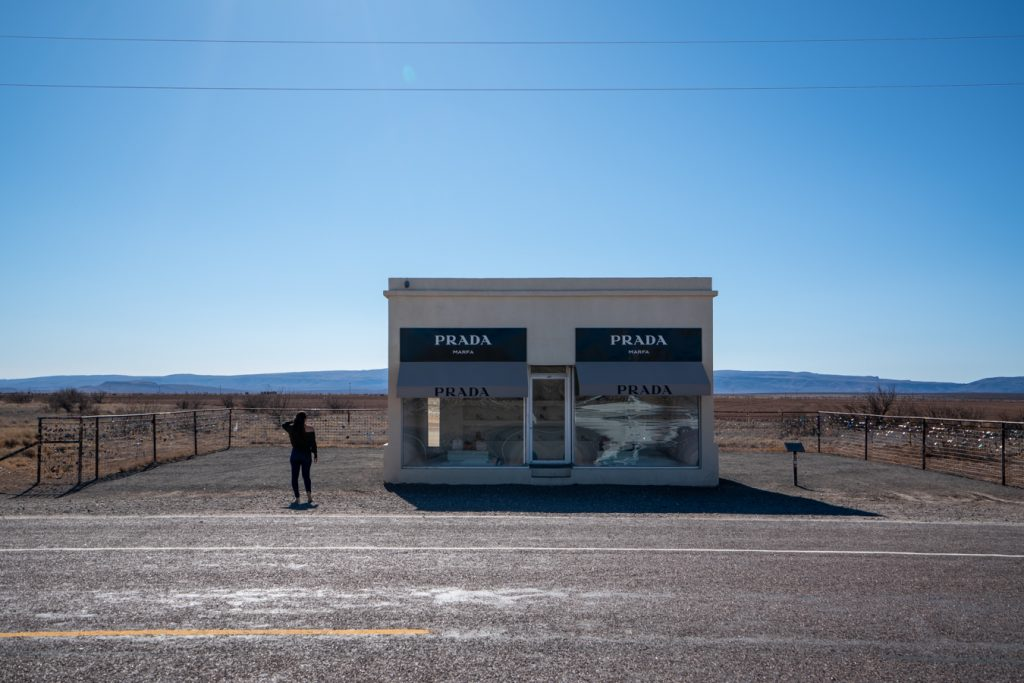kate storm in front of prada marfa in west texas, one of the best road trips in america