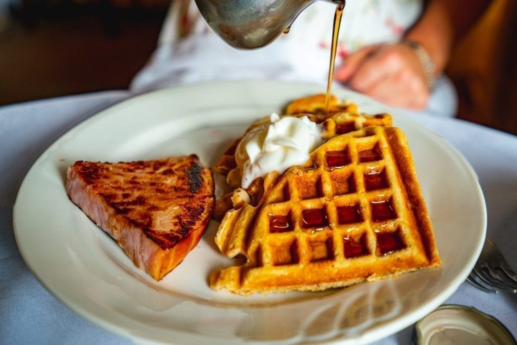 Pecan waffles with syrup being drizzled on them in Savannah GA, as seen on a weekend getaway by the author of this Savannah blog post