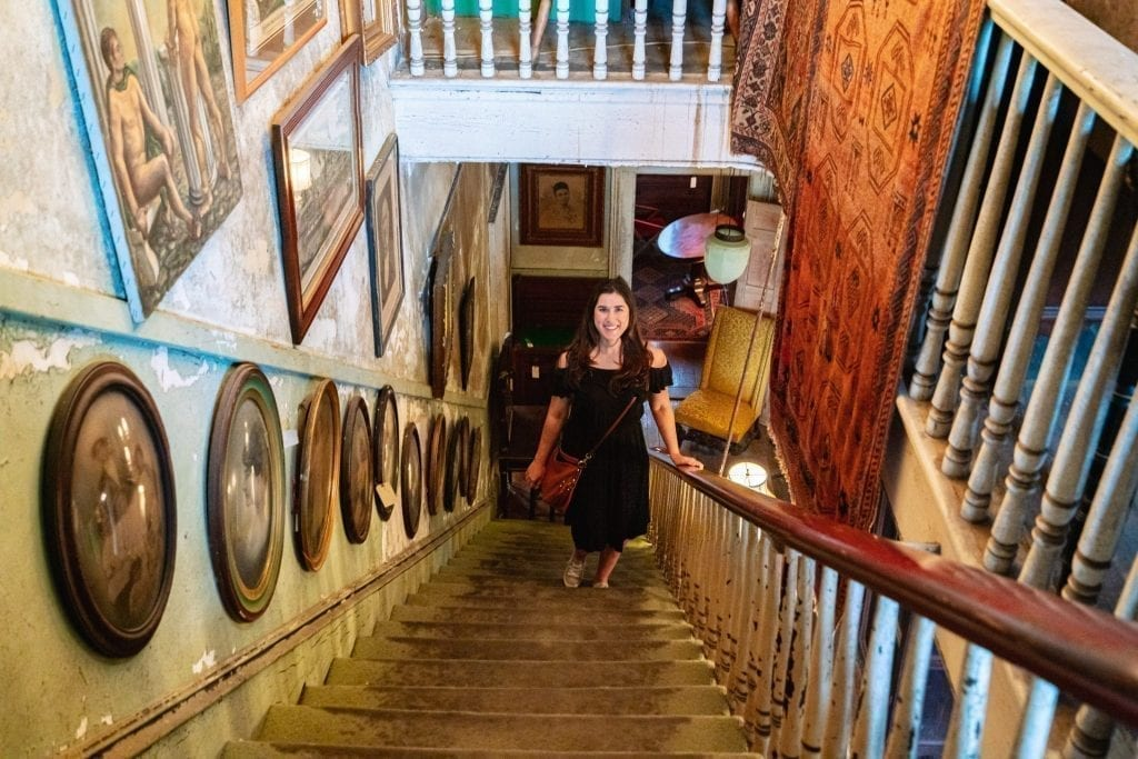Kate Storm in a black dress standing on a staircase in Alex Raskin Antiques during a long weekend in Savannah GA