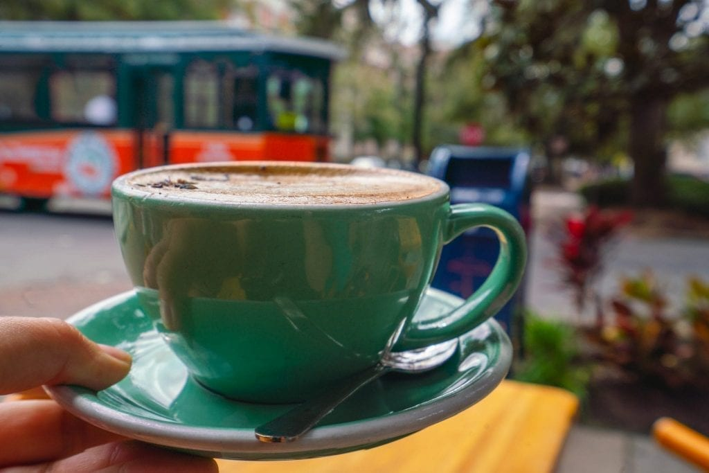 Spiced lavender mocha in a green mug being held up in front of a Savannah trolley. Coffee is from The Collins Quarter, one of the best Savannah photography locations
