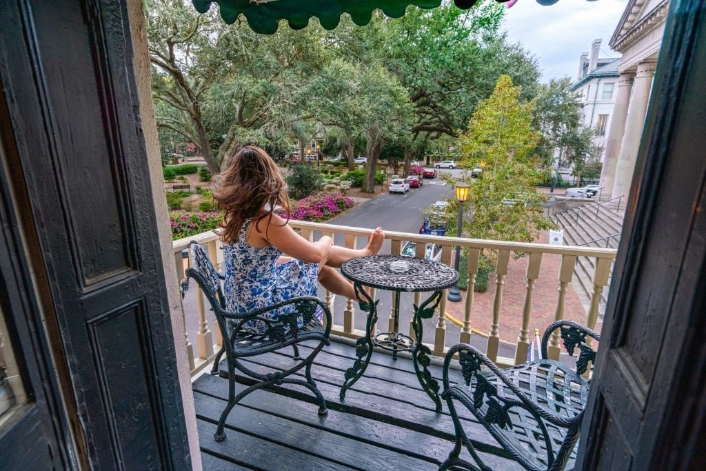 Kate Storm in a blue dress overlooking Chippewa Square from the balcony of Foley House Inn, one of the most instagrammable places in Savannah GA