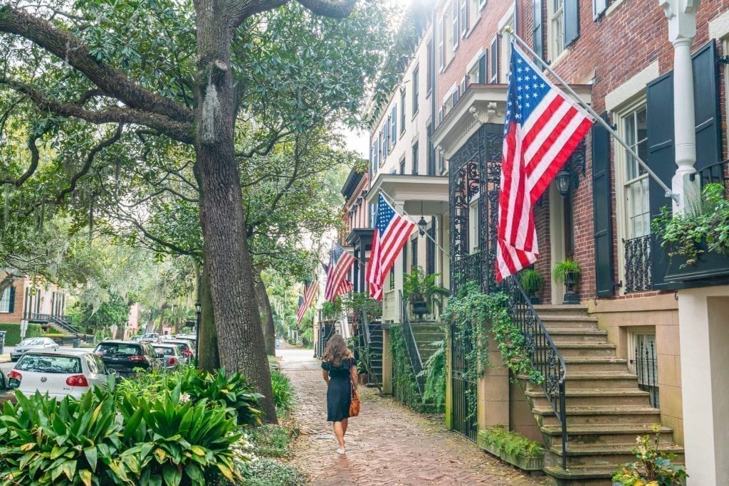 Kate Storm in a black dress walking away from the camera along Jones Steet in Savannah GA, with several American flags hanging from homes on the right side of the photo