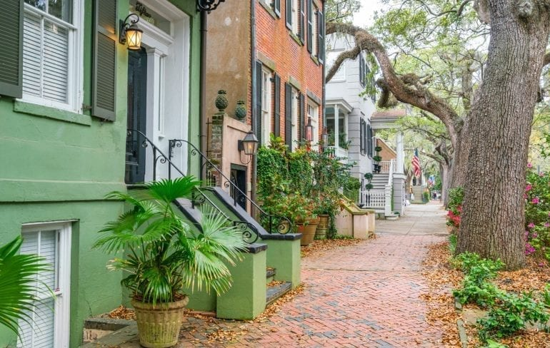 Jones Street in Savannh GA with a green house in the left foreground and an oak tree on the right. Jones Street is one of the best Savannah photo spots