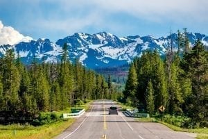 Road to Grand Tetons from Yellowstone with mountains visible in the distance, one of the best road trips in USA