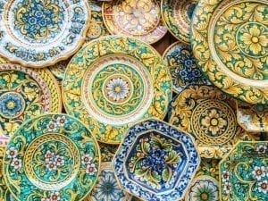 Colorful ceramic plates on display on a wall, one of the best souvenirs from Italy