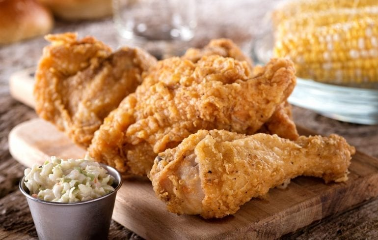 Plate of fried chicken with coleslaw on the left side and corn in the background, one of the best Lowcountry foods to eat