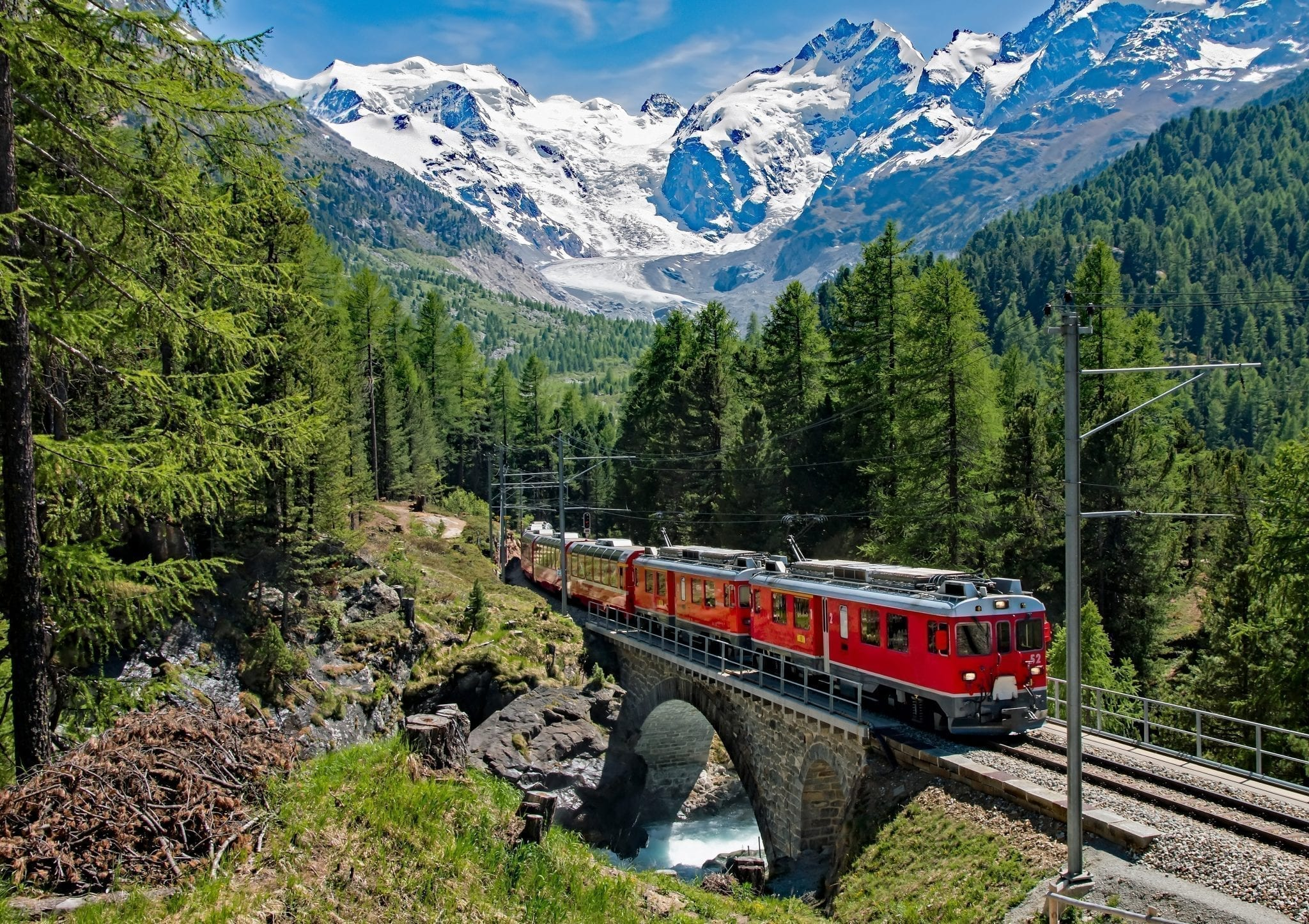 Red train moving through Switzerland with mountains visible in the background--views like this are one of the best reasons to travel Europe by train