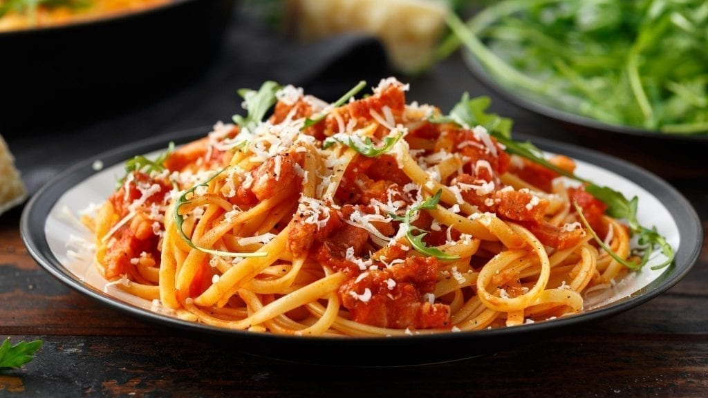 Plate of Amatriciana on a black plate. Amatriciana is a traditional food in Rome Italy
