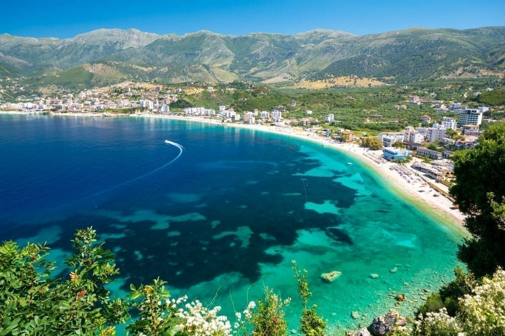 Albanian Riviera as seen from above with a boat in the distance and mountains in the background, one of the best places to vacation in Europe summer