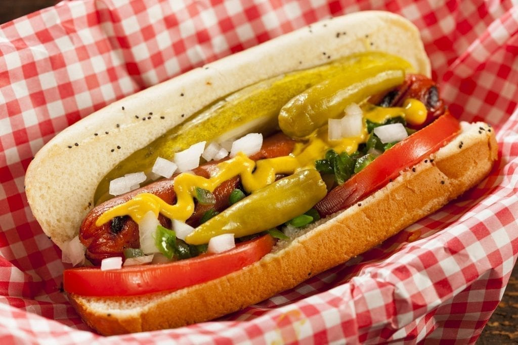 Chicago-style hot dog displayed on a red checkered napkin