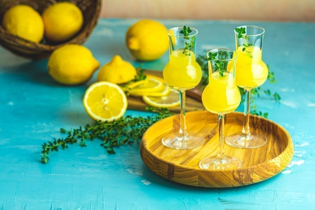 limoncello served in 3 glasses with lemons in the backgorund, one of the best italy souvenirs