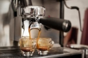 Photo of two espresso shots being filled by a machine, featured photo on our guide to how to order coffee in Italy