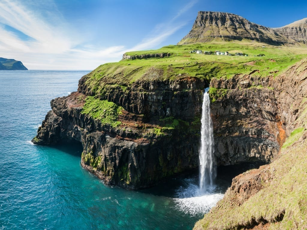Waterfall into the ocean as seen on the Faroe Islands, one of the best summer places to visit in Europe
