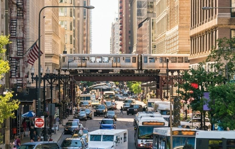 Photo of Chicago train traveling on a bridge over car traffic--using Chicago's public transportation is the best way to get around on a Chicago weekend getaway!
