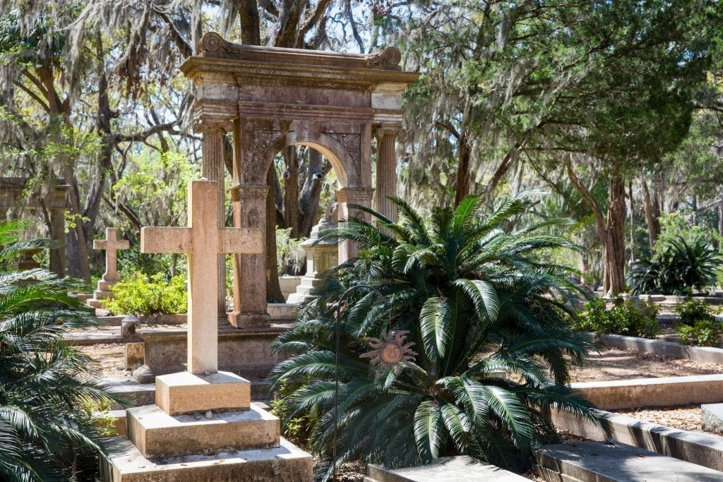 Bonaventure Cemetery in Savannah GA with a cross visible on the left and a larger statue behind it