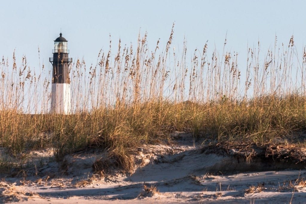 Sand dunes of Tybee Island with lighthouse visible in the back left, an easy addition to a Savannah weekend getaway