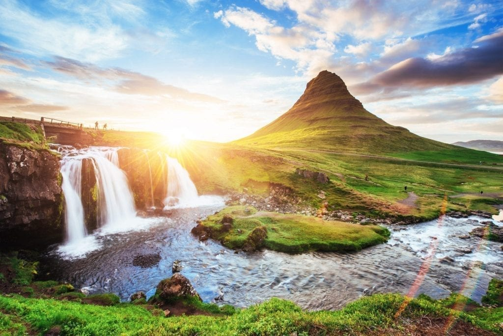 Sunset over waterfalls in Iceland, one of the best places to visit in Europe in summer