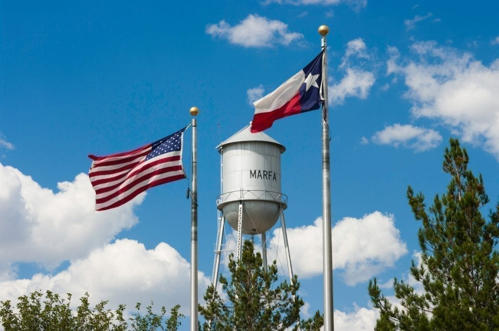 Water tower and flags flying above Marfa Texas, one of the best usa road trips in Texas