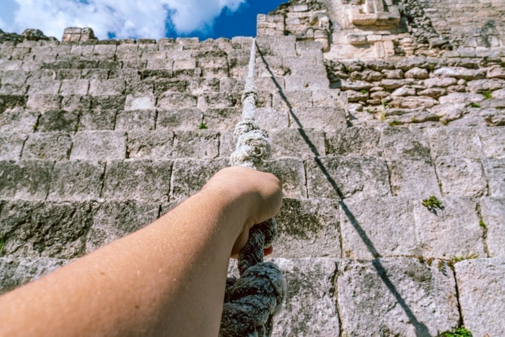 Jeremy Storm's arm reaching out and holding a rope to scale a pyramid in Becan Mayan City Mexico