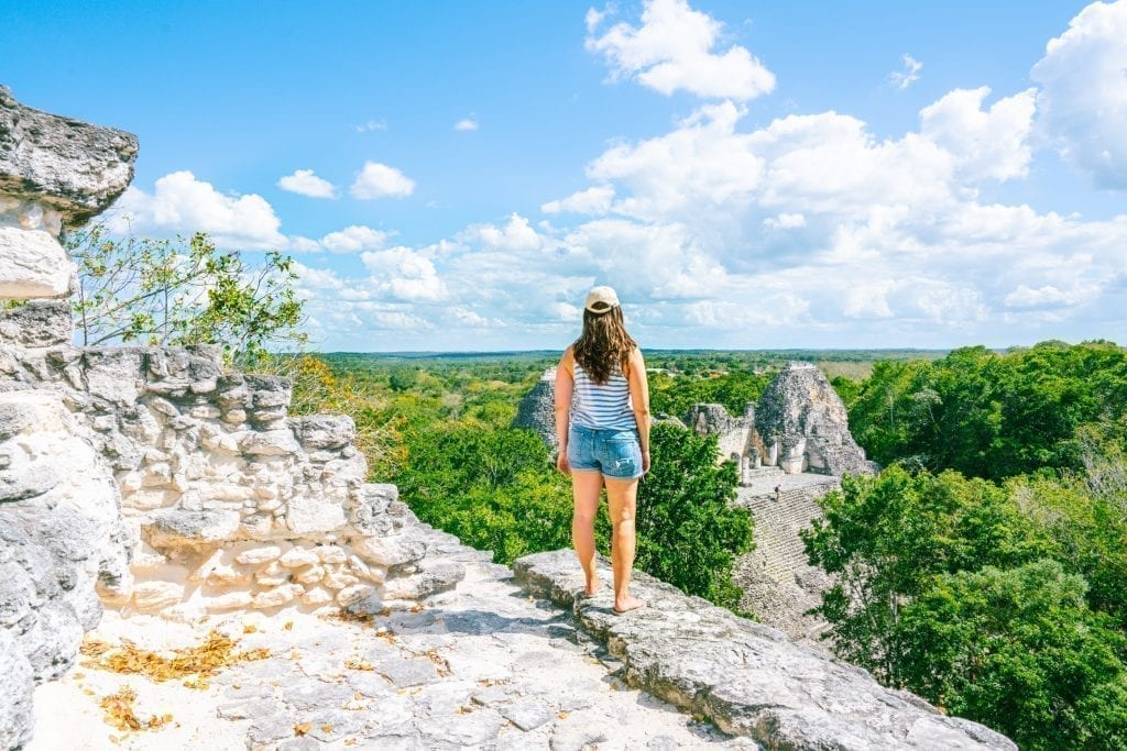 Kate Storm standing on the edge of a Mayan pyramid in Becan Mexico