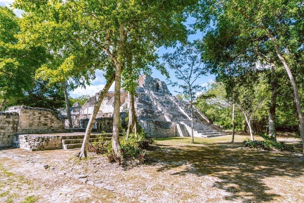 Becan Mayan ruin site in Mexico, an open plaza with a structure visible through the trees
