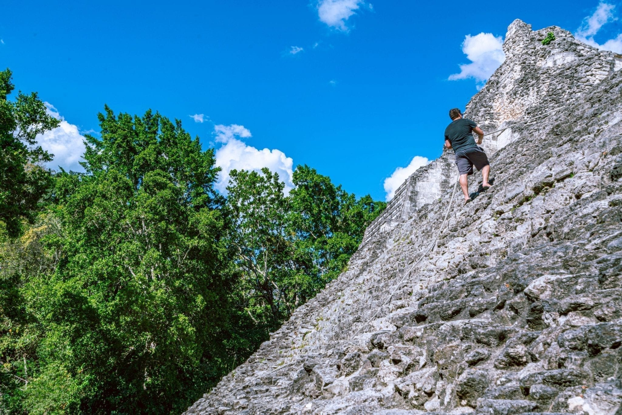 Jeremy Storm climbing a pyramid at the Becan Ruins in Mexico, wearing a black t shirt and pulling on a rope for support