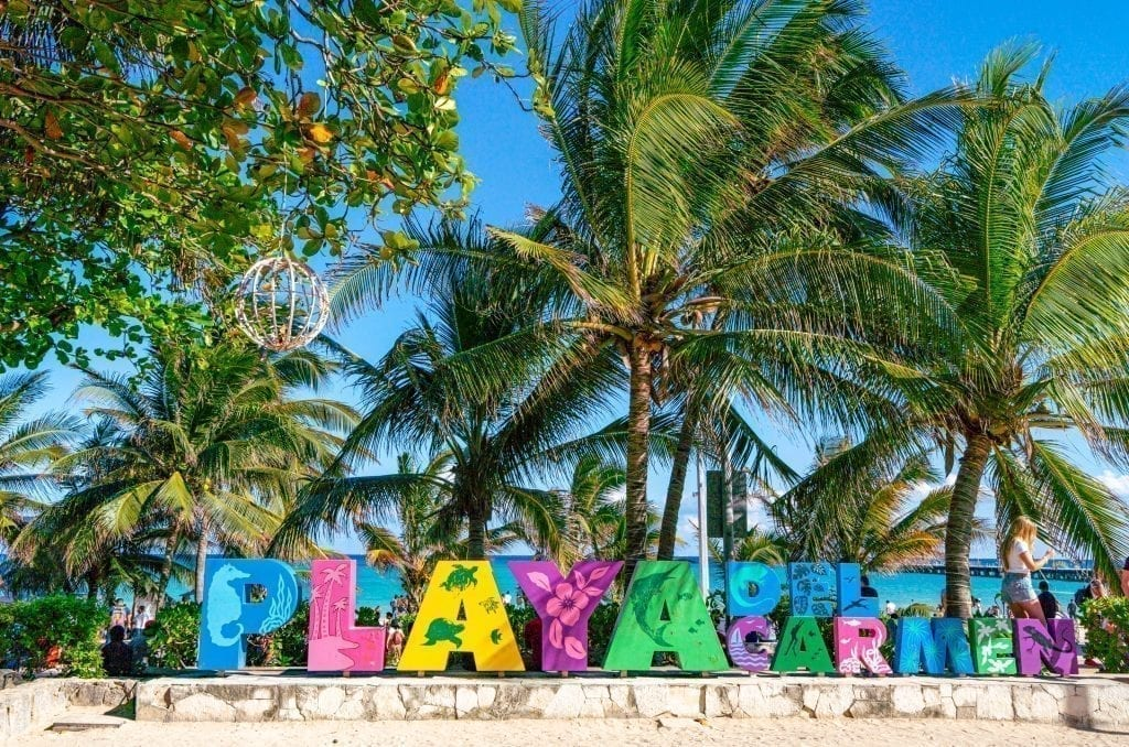 Playa del Carmen colorful sign with palm trees visible in the background