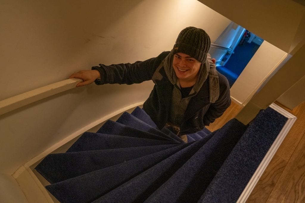 Jeremy Storm wearing a coat and hat climbing a very steep staircase in Amsterdam