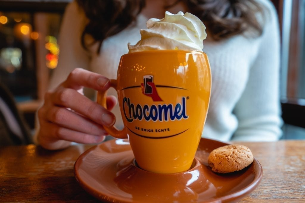 Kate Storm holding out a yellow mug of Chocmel in Amsterdam topped with whipped cream