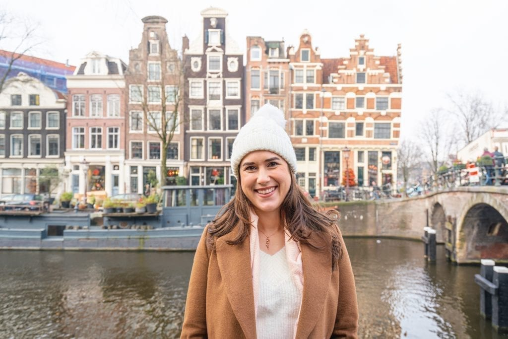 Kate Storm in a brown coat and white hat standing in front of a canal on a cloudy day in Amsterdam