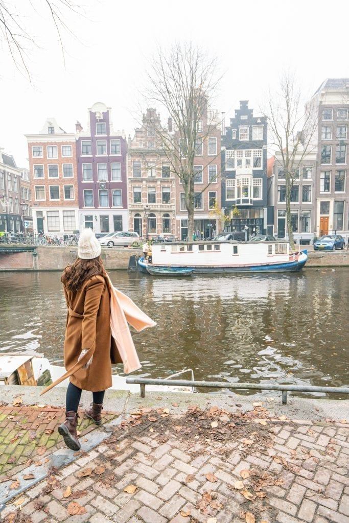 Kate Storm in a brown coat looking over a foggy canal in Amsterdam in December