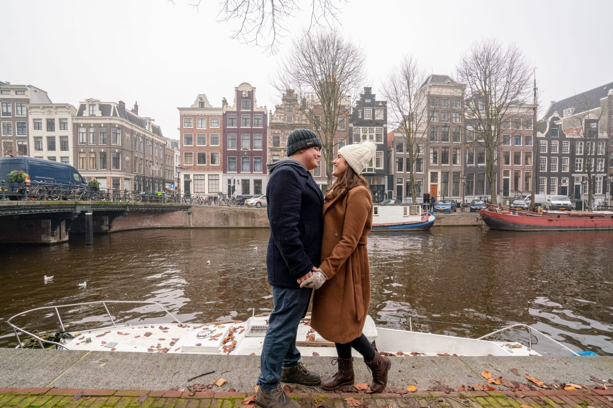 Kate Storm and Jeremy Storm wearing winter coats on the edge of a canal in Amsterdam in December, facing each other