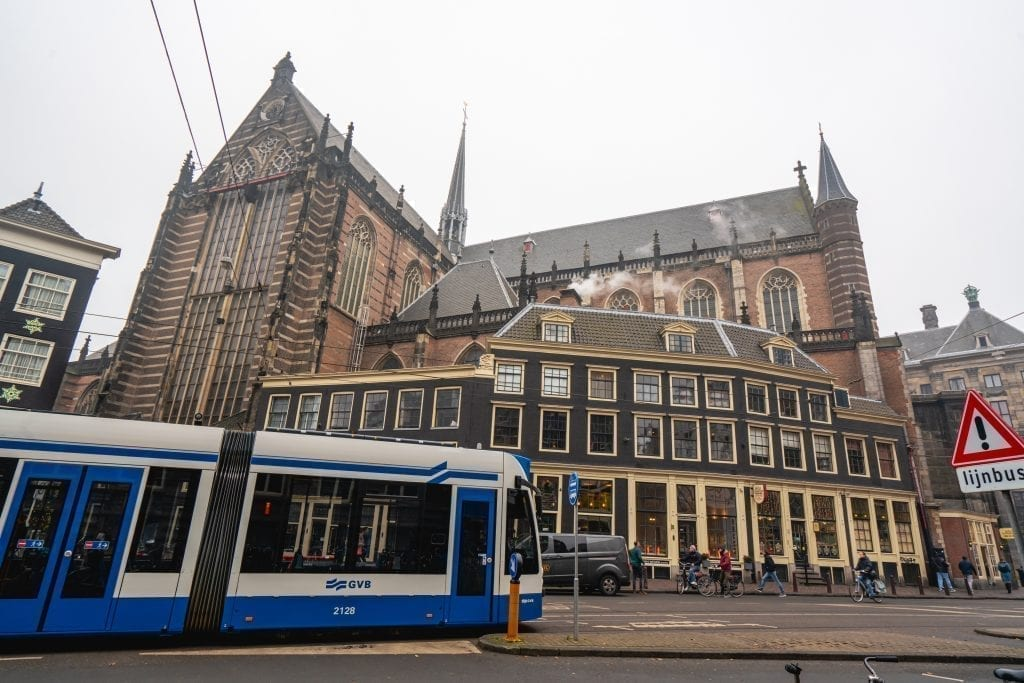 Blue and white tram in Amsterdam passing in front of a large church