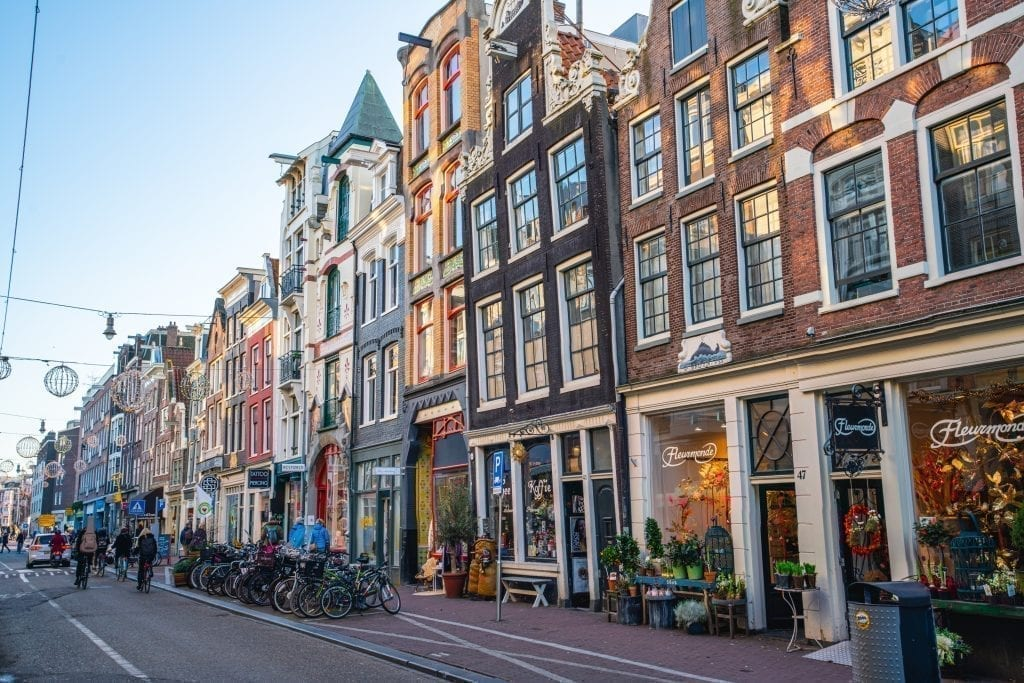 Boutiques lining a street in Amsterdam with typical Dutch houses for the city--views like these are an essential part of seeing Amsterdam in a day