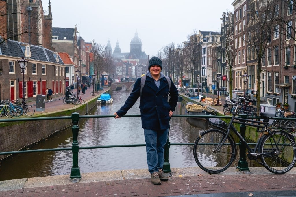 Jeremy Storm leaning against a bridge during one day in Amsterdam on a cloudy evening