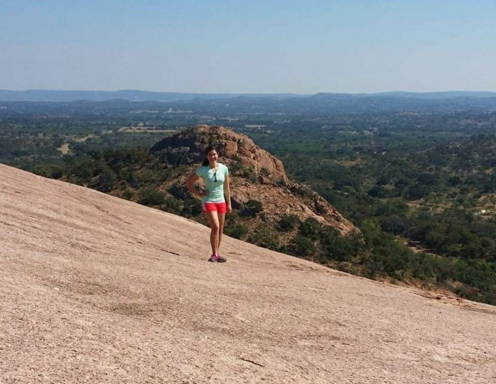 Kate Storm standing on Enchanted Rock near Fredericksburg, one of the best places to visit in Texas